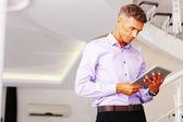Happy mature businessman using his tablet — ストック写真