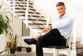 Handsome happy man on chair — Stock Photo