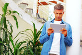 Mature casual man at home using electronic tablet — Stock Photo
