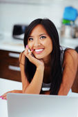 Laughing young asian woman talking on phone at home — Stock Photo