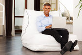Man relaxing at home in armchair with laptop — Stock Photo