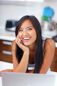 Laughing young asian woman talking on phone — Stock Photo