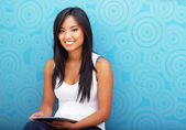 Young happy asian woman using tablet against blue background — Stock Photo