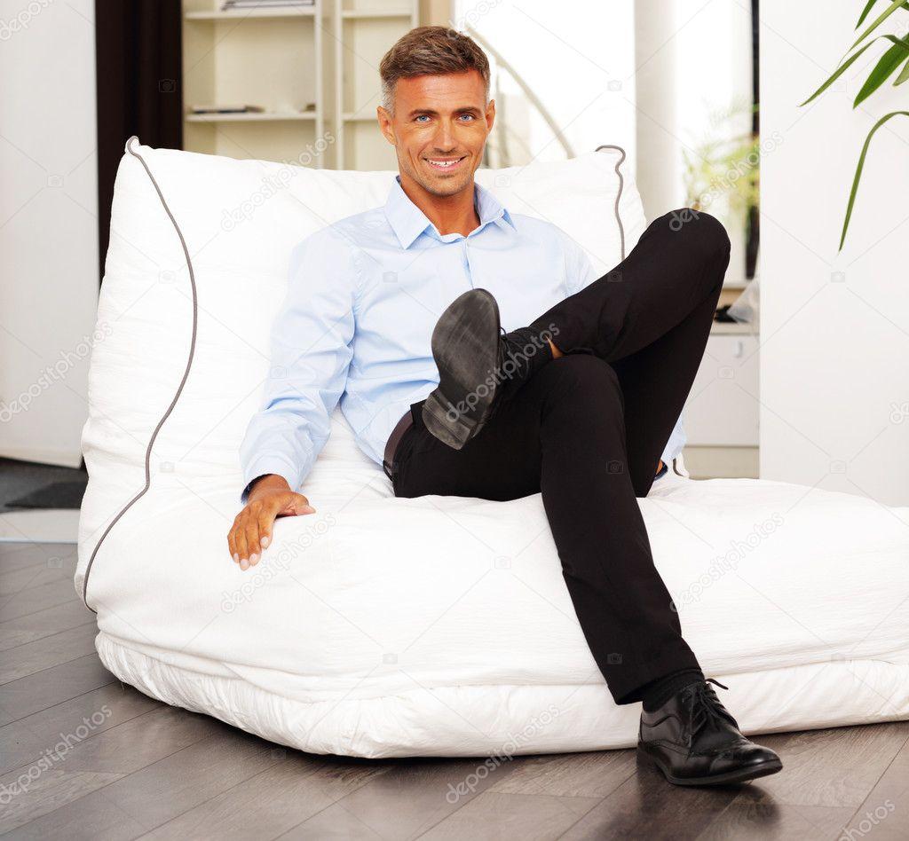 Homem confiante sentado na poltrona em casa foto stock for Sitting in armchair