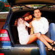 Romantic couple sitting in a trunk  — Stock Photo