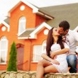 Happy couple kissing in front of new home — Stock Photo #31193589