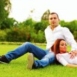 Couple resting an the lawn in park — Foto de Stock