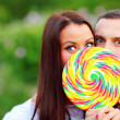 Couple covering their faces with candy — Stock Photo