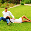 Young couple resting an the lawn in park — Stock Photo