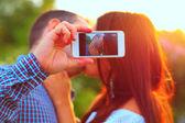 Couple taking self-portrait photos — Stock Photo