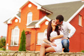 Happy couple kissing in front of new home — Stock Photo