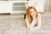 Woman lying on carpet — Stock Photo