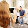 Girl making photo of family — Stockfoto