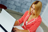 Blonde woman looking at laptop — Stock Photo