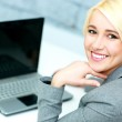 Businesswoman sitting at her workplace with laptop — Stock Photo