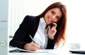 Businesswoman talking on the phone and writing notes — Stock Photo