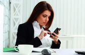 Businesswoman typing on her smartphone — Stock Photo