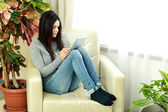 Woman sitting on the armchair with tablet computer — Stock Photo