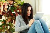 Женщина сидит на кресле с планшетного компьютера — Стоковое фото