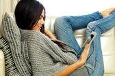 Femme, reposant sur un canapé avec tablette — Photo