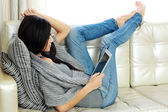 Woman resting on a sofa with tablet computer — ストック写真