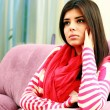 Young pensive woman sitting on the sofa — Stock Photo #39387259