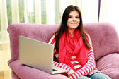Woman sitting on the sofa with laptop — Stock Photo