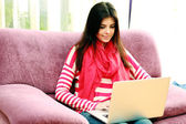 Woman sitting on the sofa and typing on a laptop — Stock Photo