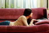Woman lying on the sofa with laptop — Stock Photo