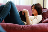 Woman lying on the sofa and reading book — Stock Photo