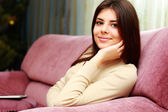 Woman sitting on the sofa at home — Stock Photo