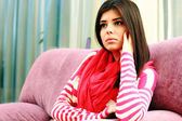 Young pensive woman sitting on the sofa — Stok fotoğraf