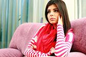 Young pensive woman sitting on the sofa — 图库照片
