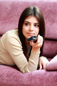 Woman lying on the sofa with remote control — Stock Photo