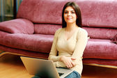 Woman sitting on the floor and using laptop — Stock Photo