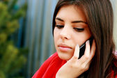 Pensive woman talking on the phone — Stock Photo