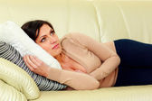 Pensive woman lying on the sofa — Stock Photo