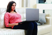 Woman sitting on the sofa with laptop — Stok fotoğraf