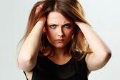 Jonge boos vrouw haar hoofd aan te raken — Stockfoto