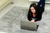 Woman lying on the carpet and using laptop — Stockfoto