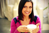 Smiling woman holding cup of coffee — Stock Photo