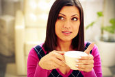 Pensive woman holding cup of coffee — Stock Photo