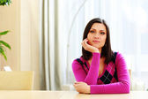 Young thoughtful woman sitting at the table — Stockfoto