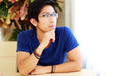 Handsome asian man at home — Stockfoto