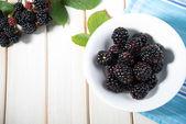 Fresh blackberries ion white plate on kitchen table — Stock Photo
