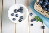 Fresh blueberries in basket on kitchen table — Stock Photo