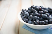 Fresh blueberries ion white plate on kitchen table — Stock Photo