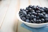 Fresh blueberries ion white plate on kitchen table — Stock Photo