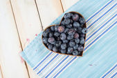 Fresh blueberries in heart shape basket on kitchen table — Stock Photo