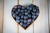 Fresh blueberries in hearth shape basket on kitchen table — Stock Photo